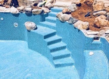 Alternative view of swimming pool with built-in rock feature, created by Almeria Builders
